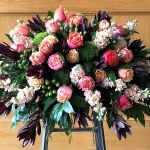 peach, coral, burgundy and green casket spray